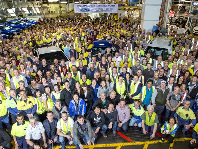 Employees gather around the world's last six-cylinder, rear-wheel drive Falcon XR6 to pose for a photo after it rolled off the assembly line at its Broadmeadows plant. Picture: Ford Motor Co. via AP