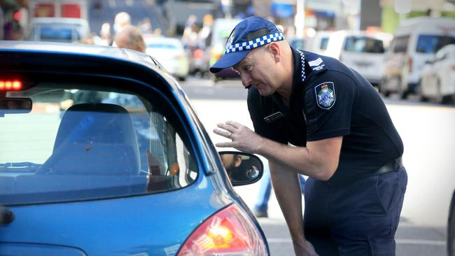 Acting Sargeant Paul Stanford talks to a motorist in Brisbane City. Picture: Jamie Hanson.