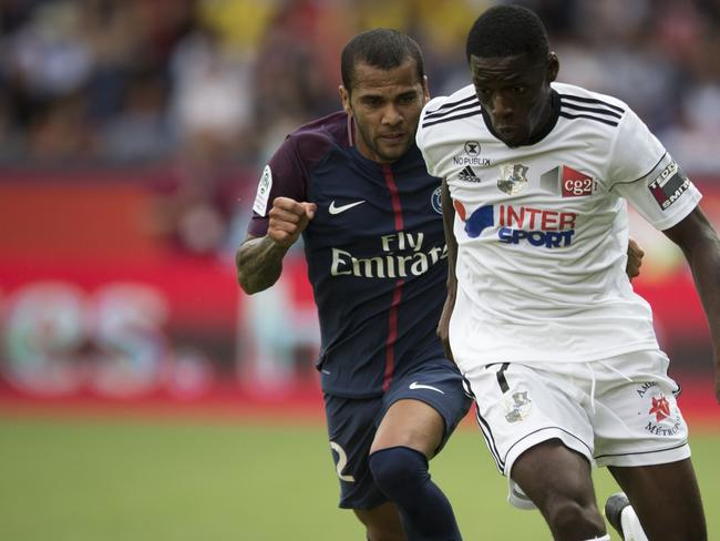 PSG's Dani Alves, left, challenges for the ball with Amien's Harrison Manzala.