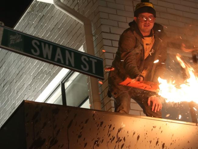 A man burns a sign in Swan Street — he was later arrested.