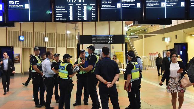 Victorian Police officers are seen inside Flagstaff train station in Melbourne. Picture: AAP Image/James Ross.