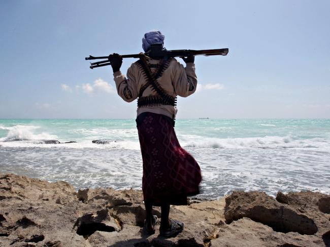 An armed Somali pirate stands on the coastline while a Greek cargo ship is seen on the horizon. Picture: AFP