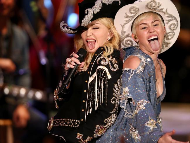Big mouths ... Madonna performs with Miley Cyrus on MTV. Picture: Christopher Polk
