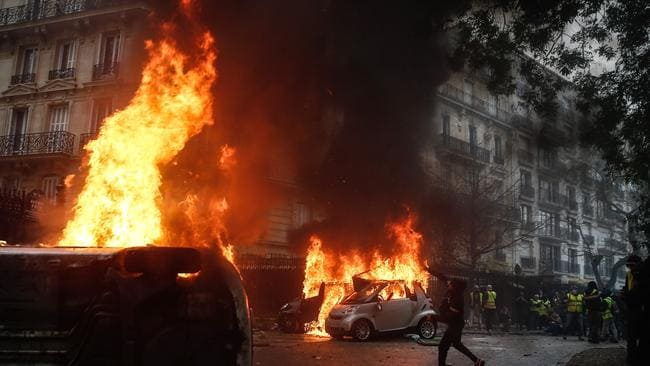 A protester throws a projectile at riot police near burning cars during a protest of Yellow vests. Picture: AFP