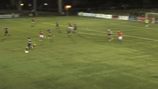 Danny Choi kicks the ball from inside his own half.