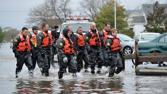 New York Police Department divers walk through a flooded area in the Breezy Point area of Queens in New York that was hit hard by Hurricane Sandy. Picture: Stan HONDA