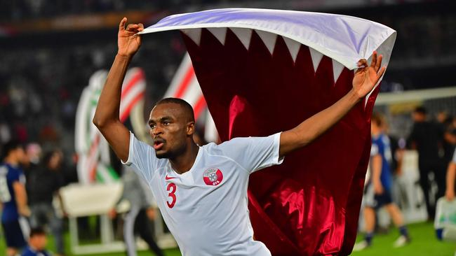Qatar's defender AbdelKarim Hassan waves the national flag as he celebrates
