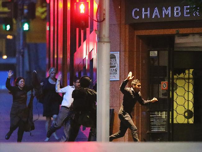 Hostages flee the Lindt Cafe last night. Picture: Joosep Martinson/Getty Images