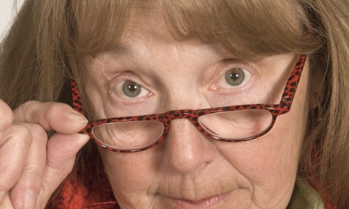 Close up of a senior adult female wearing glasses pursing her lips in disapproval at the camera. This senior citizen wants to tell the viewer exactly what she thinks, because her opinion should be just as important as yours!