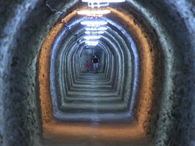 Walking down the narrow, flickering tunnels inside Salina Turda. Picture: Flickr/Cristian Bortes