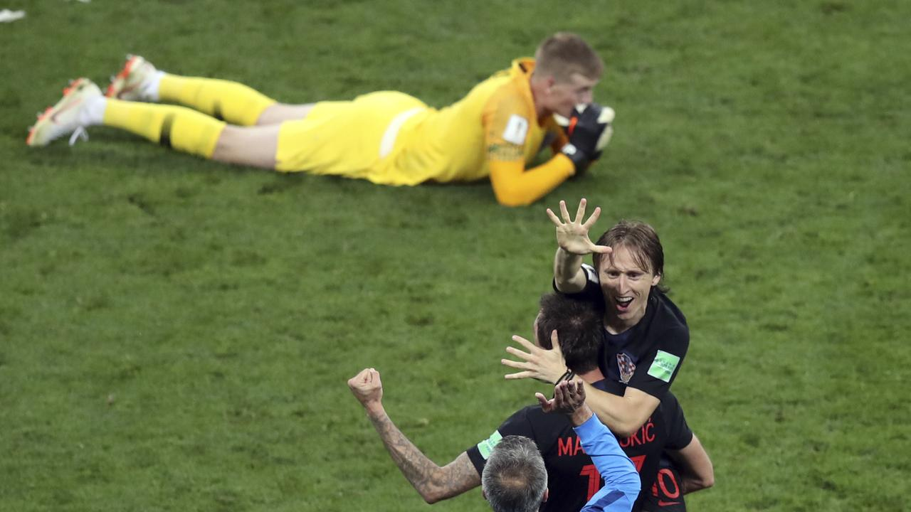 Croatia's Luka Modric, right, celebrates next to England goalkeeper Jordan Pickford, on the ground, at the end of the semifinal