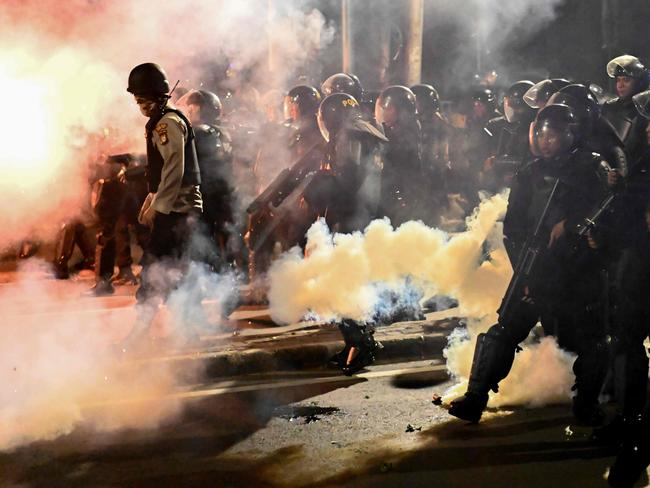Indonesian police wade through tear gas fired at demonstrators. Picture: AFP