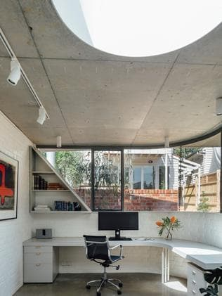 The desk is shaded by the curved extended eave outside.
