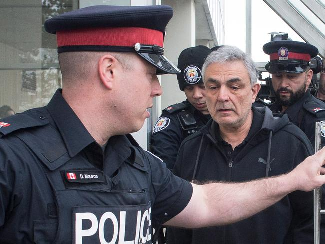 Vahe Minassian surrounded by members of the media as he leaves court with a police escort. Picture: Chris Young/The Canadian Press via AP