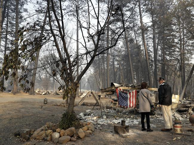 President Donald Trump talks to Mayor Jody Jones as he visits a neighborhood impacted by the wildfires. Picture: AP