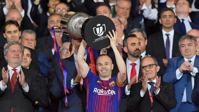 Barcelona's Spanish midfielder Andres Iniesta (C) holds the trophy after the Spanish Copa del Rey (King's Cup) final