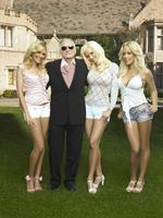 "Playboy magazine founder Hugh Hefner with Playboy models, Holly Madison in scene from TV programme ""Girls of a Playboy Mansion""."
