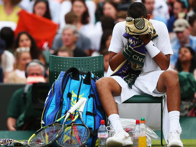 Nick Kyrgios sits dejected at the conclusion of his quarter-final match against Milos Raonic.
