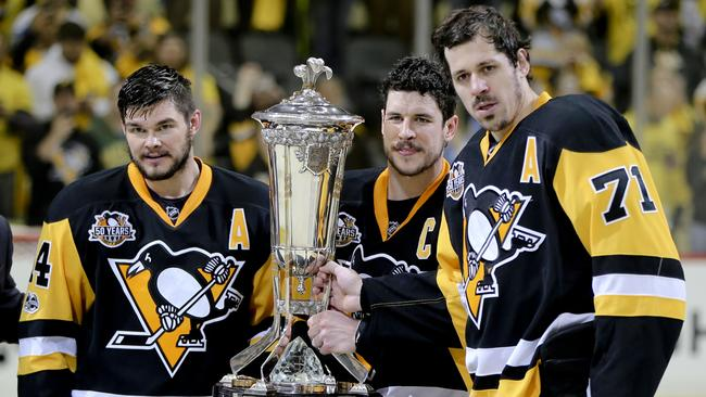 Pittsburgh Penguins' team captain Sidney Crosby (87) holds the Prince of Wales Trophy and poses with assistant captains Evgeni Malkin (71) and Chris Kunitz (14) after defeating the Ottawa Senators.