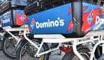 Domino's Pizza delivery bicycles are seen outside a Domino's store in Brisbane, Tuesday, August 14, 2018. Strong consumer demand for Domino's Pizza's has helped the chain deliver an 18 per cent rise in annual net profit to $121.5 million. (AAP Image/Darren England) NO ARCHIVING