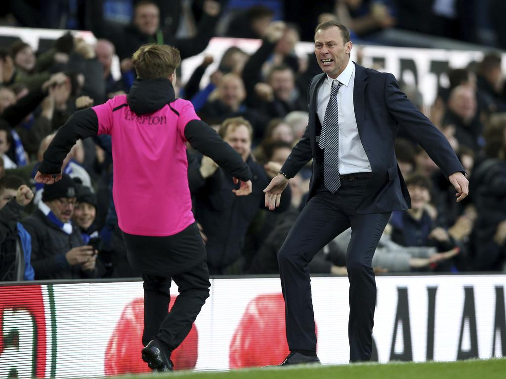 Everton caretaker manager Duncan Ferguson celebrates with a ball boy after seeing his side score their third goal, during the English Premier League soccer match between Everton and Chelsea at Goodison Park, in Liverpool, England, Saturday, Dec. 7, 2019. (Nigel French/PA via AP)