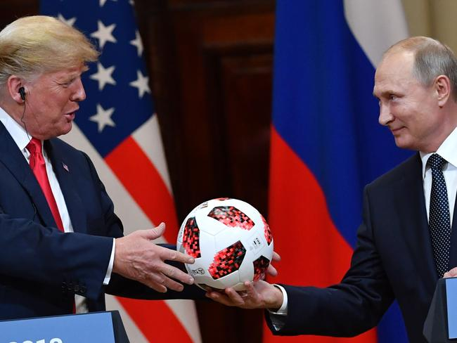 Russia's President Vladimir Putin offers a ball of the 2018 football World Cup to US President Donald Trump. Picture: AFP