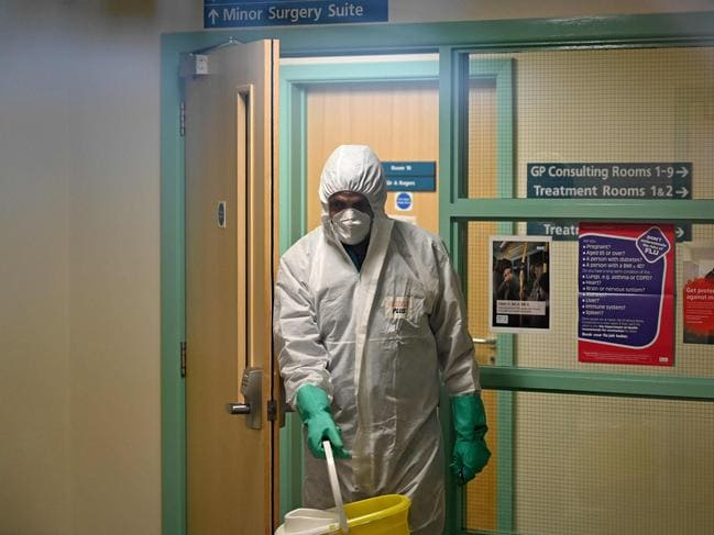 "A worker in protective clothing cleans down a GP practice which closed for ""urgent operational health and safety reasons"" after a doctor was infected with the coronavirus. Picture: Glyn KIRK / AFP."
