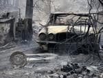 The burnt out shell of a Jaguar vehicle sits in the ruins of a smouldering house on Old Bar road Near Taree, NSW, Saturday, November 9, 2019. Two people have been killed and seven others are missing in bushfires in NSW which have also destroyed at least 100 homes. (AAP Image/Darren Pateman)