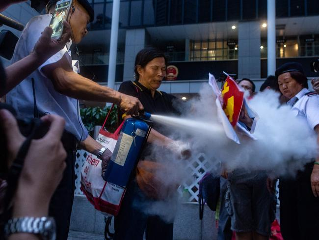 A security guard extinguishes a burning portrait of Chinese leader Xi Jinping held by a pro-democracy activist during a protest march by thousands in Hong Kong. Picture: AFP