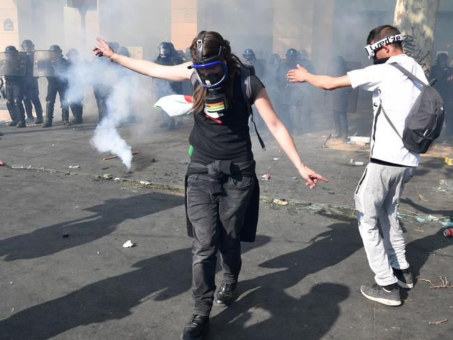 A hooded demonstrator is pictured as riot police fire tear gas. Picture: Getty Images
