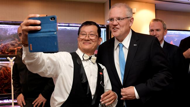 The PM takes a selfie with one of the waiters. Picture: Tracey Nearmy/Getty Images