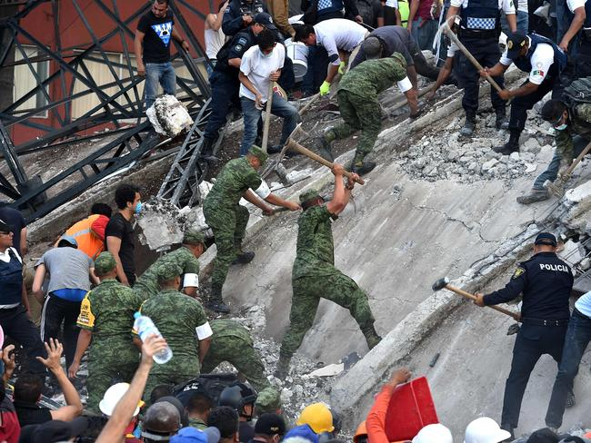 Rescuers, firefighters, policemen, soldiers and volunteers remove rubble and debris from a flattened building in search of survivors. Picture: AFP / YURI CORTEZ