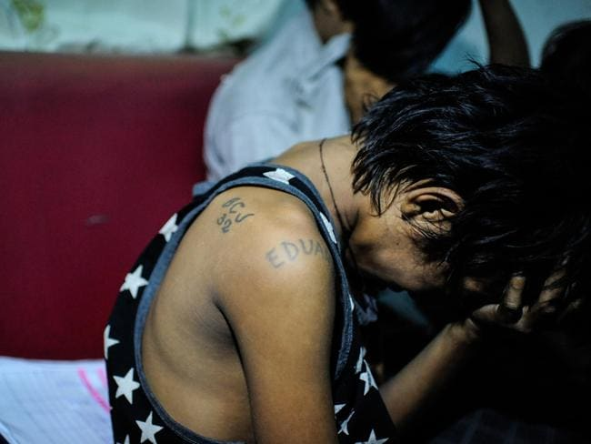 Eduardo, a 13-year-old underage member of a prison gang is picked up by police during a night time drug raid in a shanty community in Manila in June. The youngster is one of thousands to be targeted by a tough crackdown on criminal activity. Picture: Dondi Tawatao