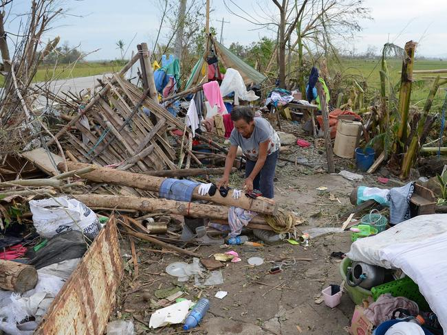 A woman dries belongings among the ruins of their house in the aftermath of Super Typhoon Mangkhut in Cagayan province, the Philippines. Picture: AFP