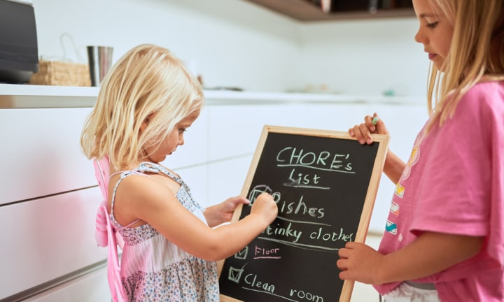 Shot of two little girls writing a list of chores on a chalkboard at home