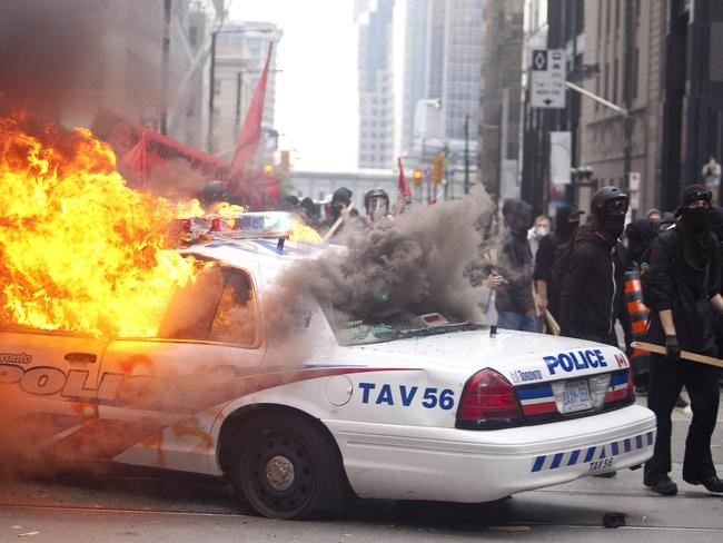 Protesters smash police vehicles in Toronto in 2010. Picture: AFP/Geoff Robins