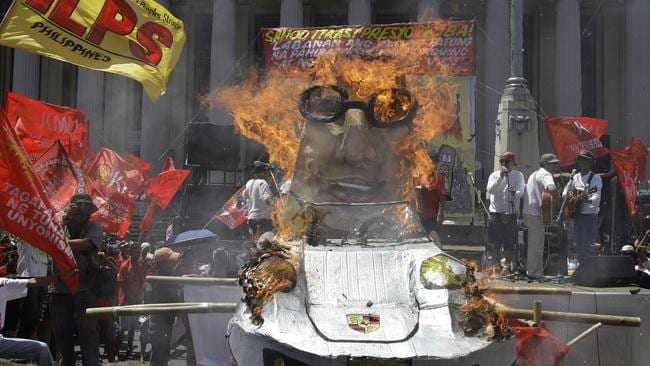 Protesters burned an effigy of Philippine President Benigno Aquino III on a luxury car during a Labour Day rally in Manilla. Picture: Aaron Favila