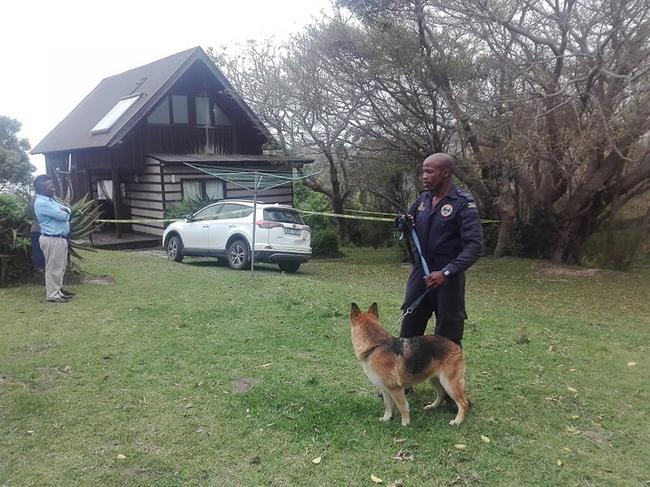 A police sniffer dog handler searches for clues near the chalet where Karen Turner was stabbed to death and her husband Matthew critically wounded. Picture: Supplied