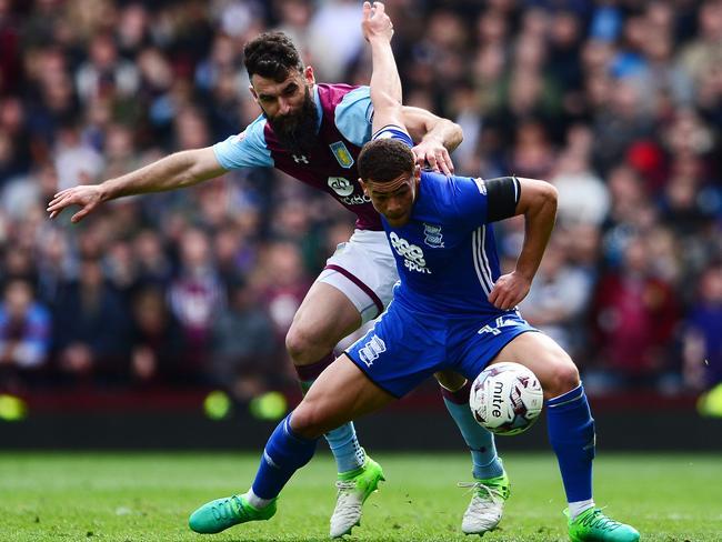 Che Adams of Birmingham City is tackled by Mile Jedinak of Aston Villa.