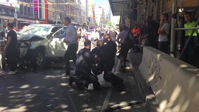 Man handcuffed at the scene of Flinders Street incident