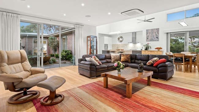 Sliding doors connect the living room to multiple outdoor areas.