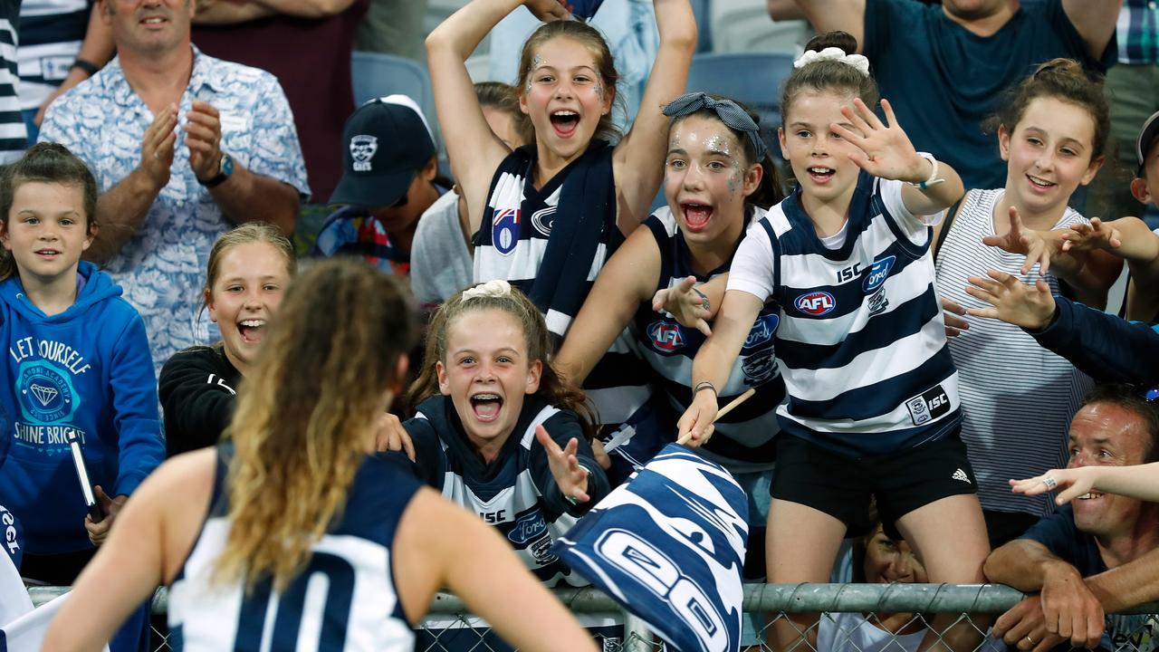 A cheering crowd in the stands at an AFLW game, young girls in their team colours excitedly wave and holler at a player