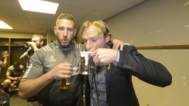 Crusaders lock Luke Romano and coach Scott Robertson share a victory drink.
