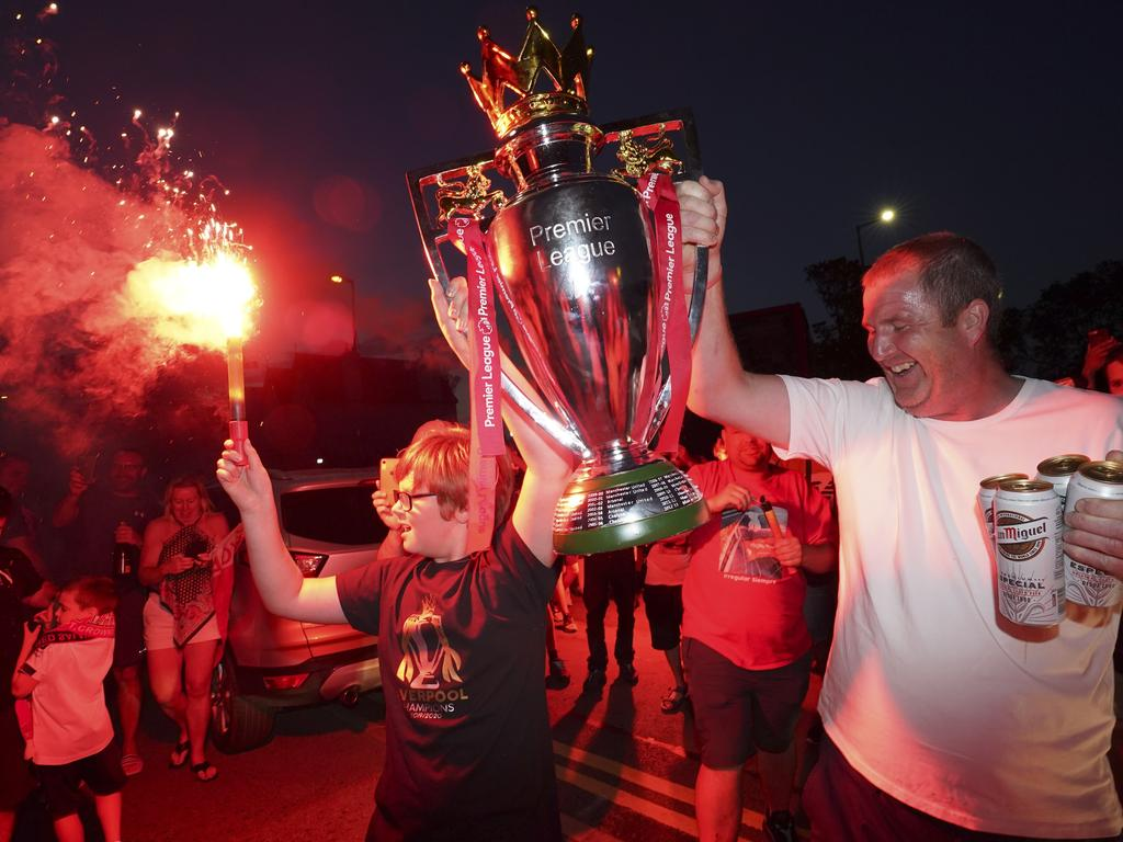 Liverpool supporters hold a replica Premier League trophy as they celebrate outside of Anfield Stadium.