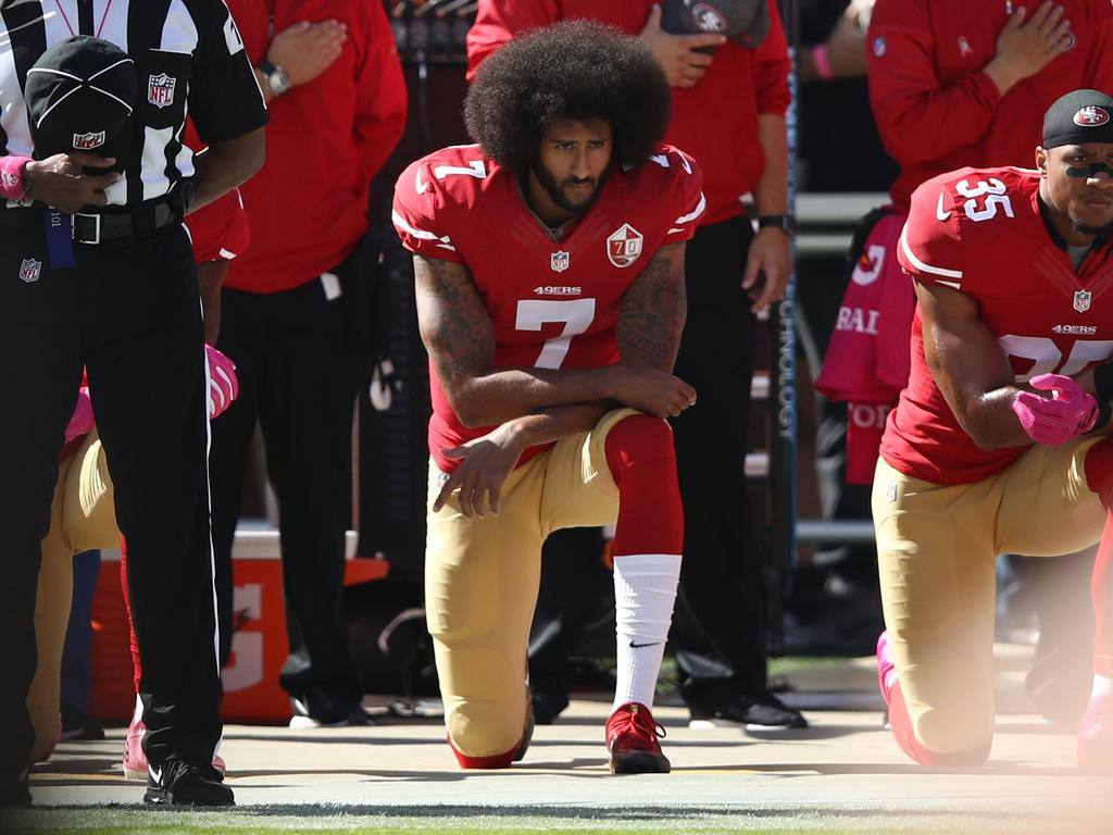 Colin Kaepernick (C) and Eric Reid (R) of the San Francisco 49ers kneel in protest during the national anthem in 2016. The Black Lives Matter movement in the US has prompted a re-evaluation of racism in Australian sport. Picture: EZRA SHAW / GETTY IMAGES NORTH AMERICA / AFP