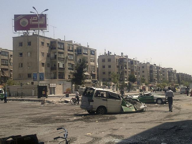 Syrians walking past destroyed vehicles after fighting between rebels and Syrian troops in the Yarmouk camp.