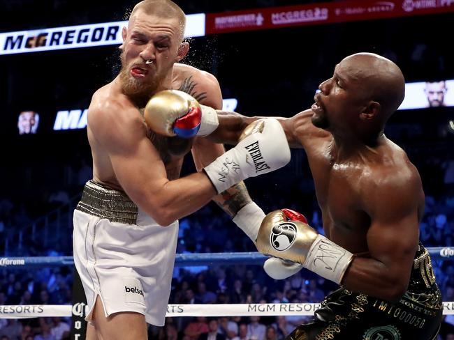 Floyd Mayweather Jr. throws a punch at Conor McGregor during their super welterweight boxing match on August 26, 2017 at T-Mobile Arena in Las Vegas, Nevada. (Photo by Christian Petersen/Getty Images)