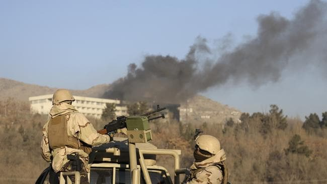 Afghan security personnel stand guard as smoke rises from the Intercontinental Hotel. Picture: Rahmat Gul/AP