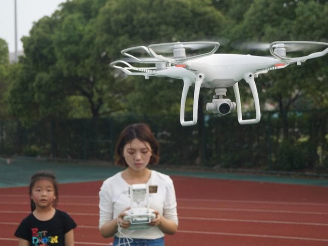 A woman operates an unmanned aerial vehicle (UAV), or drone, of DJI (Dajiang Innovations), in Suzhou city, east China's Jiangsu province, 11 May 2017. Picture: Supplied
