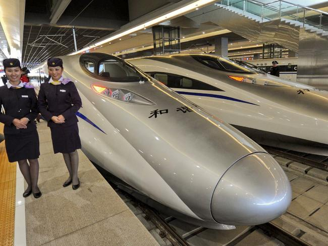 Rail attendants pose with Chinese high-speed trains at a station in Shanghai.